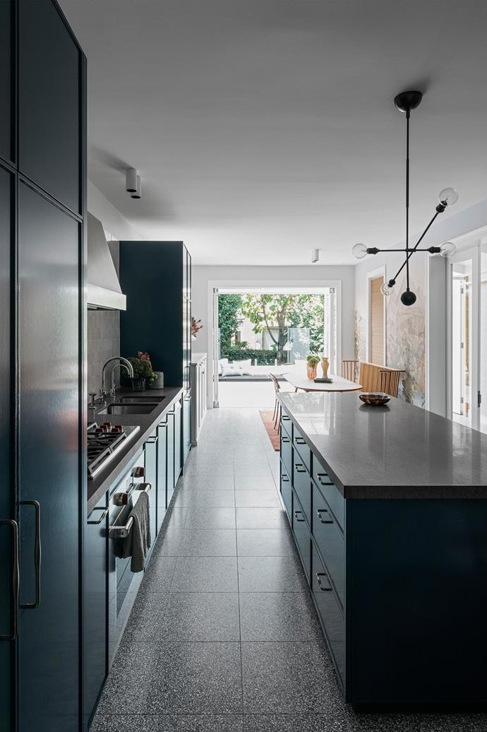 The bold navy of the kitchen cabinetry contrasts with the natural finishes and white walls of the open-plan kitchen and living spaces.