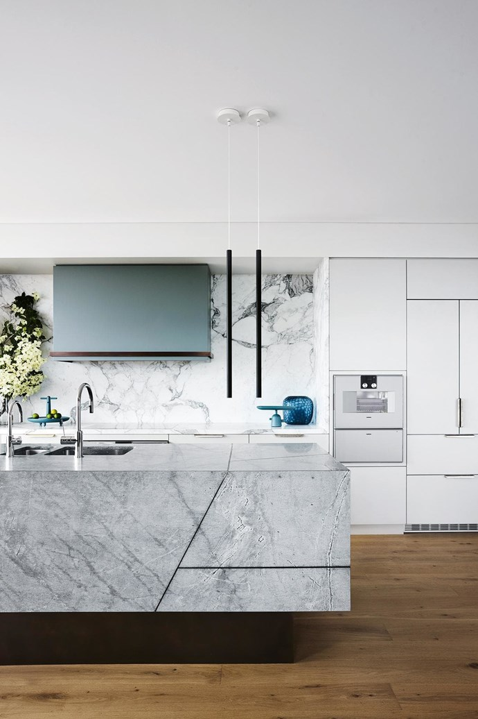 """**Stone age** Sculptural form meets function in this contemporary and efficient layout. Embellished with a richly detailed marble countertop and splashback, the giant island bench is seemingly hewn from raw stone, defining the space with its impressive presence. Shades of grey and white on the rangehood and cabinetry are lifted by flashes of brass from the bespoke Henry Wilson drawer pulls. Design: [Arent & Pyke](http://arentpyke.com/