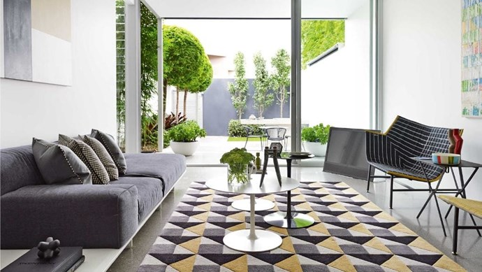 The courtyard serves as a lush green bookend to the open plan living area. A cluster of MDF Italia 'Flow' tables in a range of heights are a dynamic addition to the zone. Photographer: Anson Smart