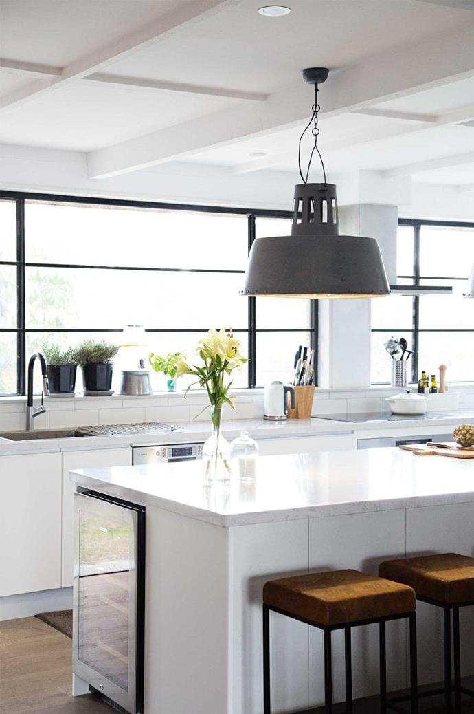 The aluminium window frames and industrial style pendant light give this sleek white kitchen a cool edge. Photography: Sneh Roy Photographer: Sneh Roy