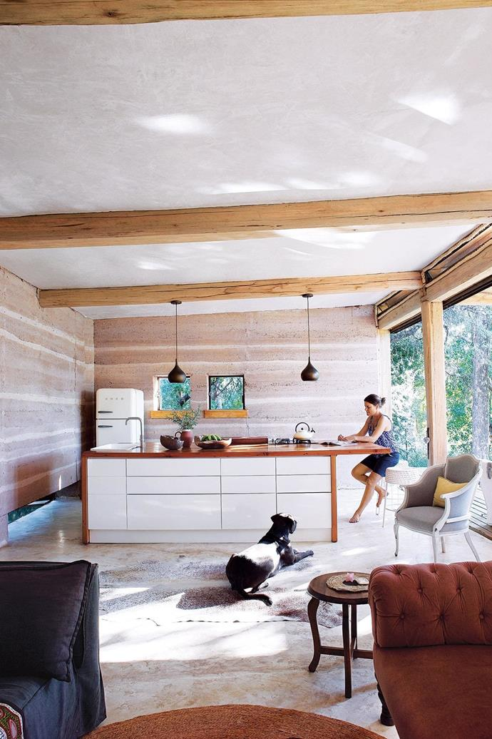 """**Kitchen** Darryl relaxes with her dog Gatsby. Her kitchen island has storage on both sides, and the flooring throughout is a cement screed, using white cement for a limewash effect. Pendant lights, [Weylandts](https://www.weylandts.co.za/). [Read the full story here](https://www.homestolove.com.au/building-a-sustainable-rammed-earth-home-in-botswana-15548