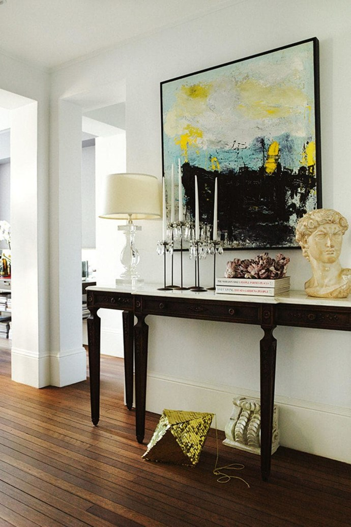 A large painting and a group of thoughtfully arranged objects upon a restored vintage marble-topped French console table make for a visually stunning display. *Photographer: Prue Ruscoe.*