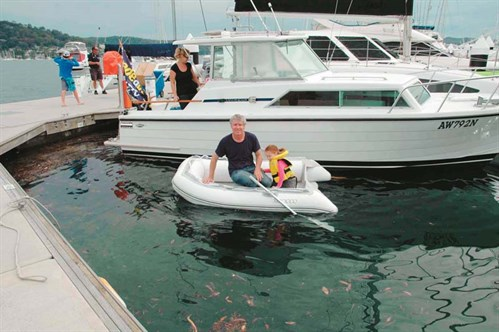 Sailor in a dingy at a marina.