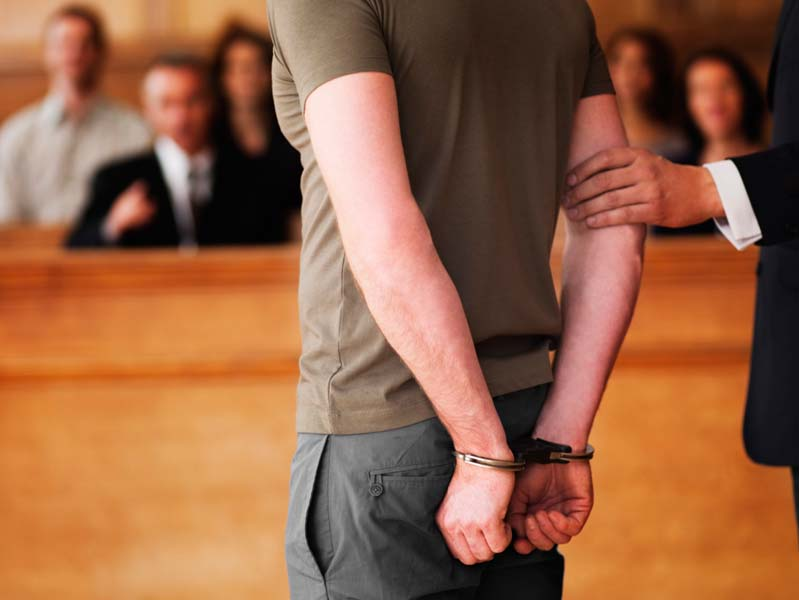 Man in handcuffs standing in court