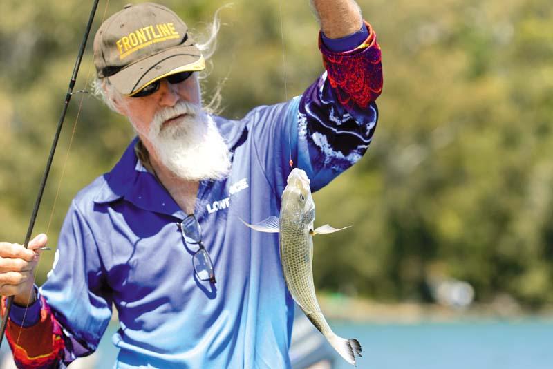 Elderly angler holding caught fish