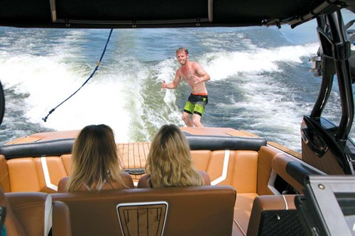 Wake surfer behind Nautique wakeboat