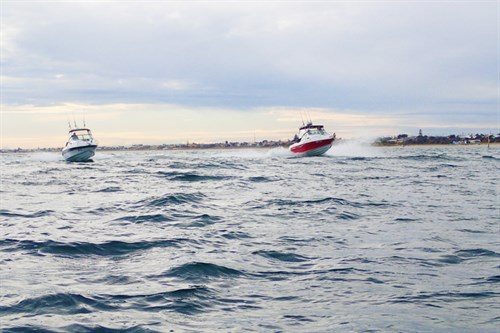 Two fishing boats racing ahead on rough water