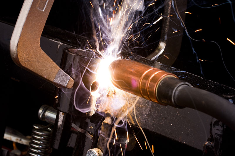 Worker uses a MIG welder