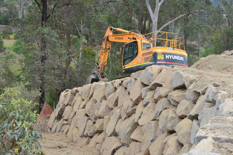 Hyundai excavator on rock wall