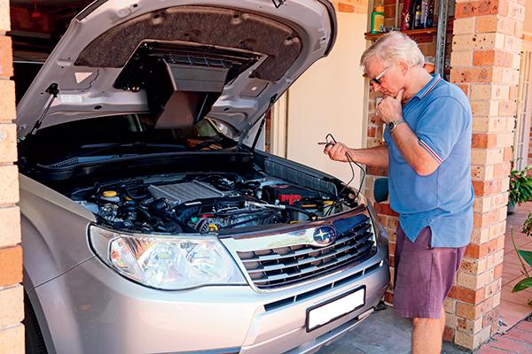 A-man -looking -at -car 's -wirings