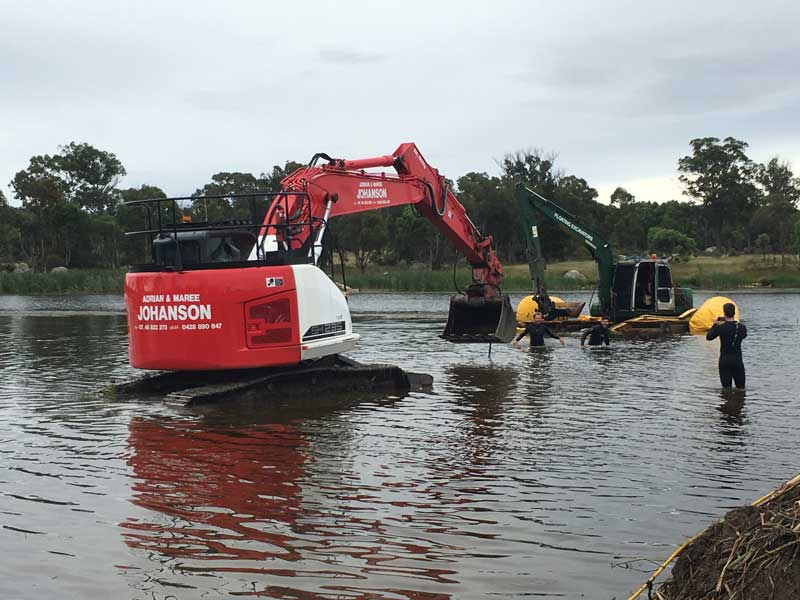 Excavators in lake