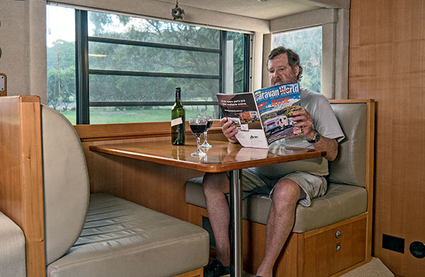 Trevor -reading -Caravan -World -magazine -while -sitting -at -cafe -dinette -in -his -customised -Denning -motorhome