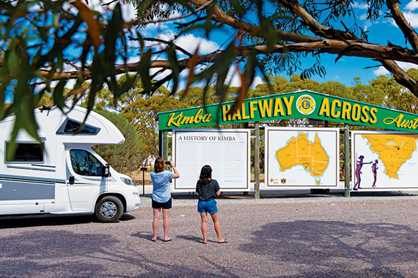Two -women -standing -at -the -Kimba -Halfway -Across -Australia -sign -in -SA