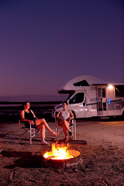 Two -women -sit -by -the -campfire -next -to -Avida -Birdsville