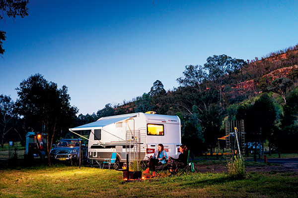 Two -women -sitting -next -to -Adria -caravan -in -Warrumbungle -National -Park -NSW