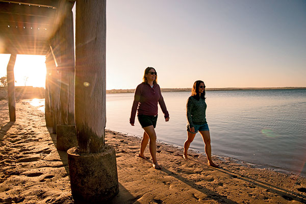 Two -women -walking -under -the -jetty -in -Eyre -Peninsula -SA