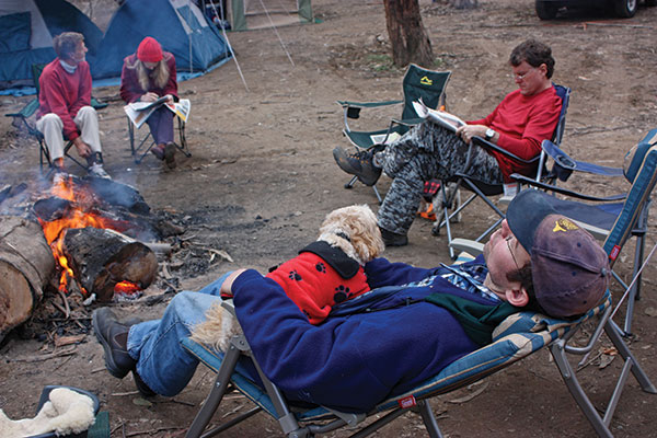 People -sitting -by -the -campfire -with -a -dog