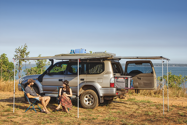 People -sitting -next -to -a -4WD-camping -setup