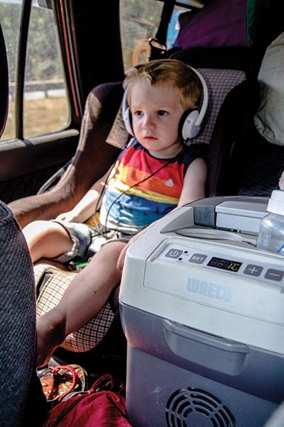 Kid -in -headphones -sitting -in -the -car -next -to -the -centre -console -fridge