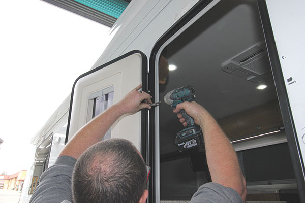 The -old -caravan -door -is -unscrewed -at -the -hinges -and -removed