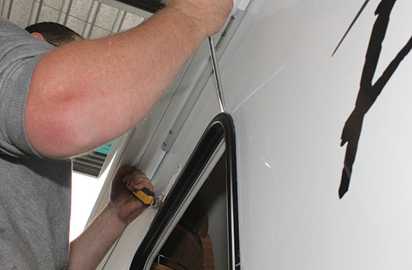 Cutting -through -the -glue -on -the -outer -caravan -door -frame -area -and -prising -the -frame -away -from -the -body