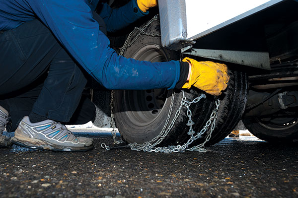 Man -putting -snow -chains -on -wheels -of -a -motorhome