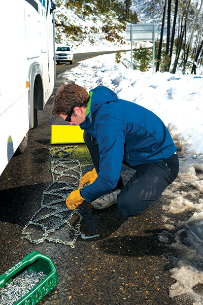 Man -putting -snow -chains -on -wheels -of -a -motorhome -2