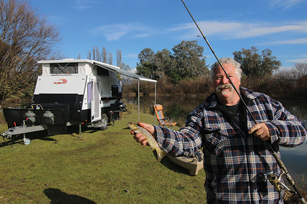 Man -fishing -at -the -lake -holding -a -fish -next -to -a -caravan