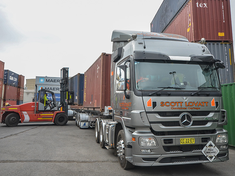 Empty containers getting loaded onto a Scott Lovatt Container Cartage truck