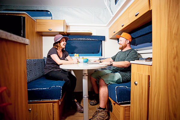 Two -people -sitting -in -a -dinette -in -a -caravan