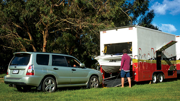 Man -loading -up -a -Quintrex -tinnie -boat -and -Ford -Forester -into -a -custom -built -motorhome