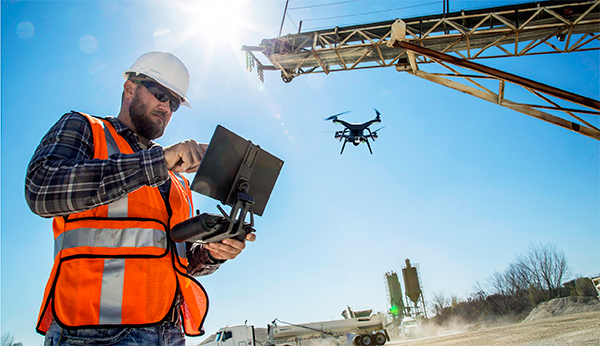 Construction worker operating drone