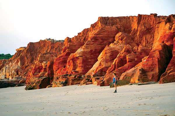 Woman -standing -at -the -beach -next -to -red -rock -formations