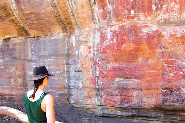 Woman -looking -at -Australia 's -Indigenous -drawings -on -the -stone