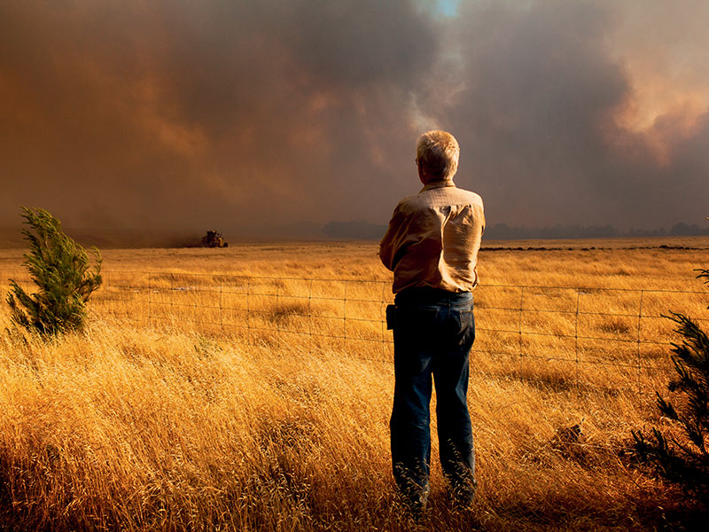 A farmer watches on as a grader creates a fire break near Port Lincoln, SA