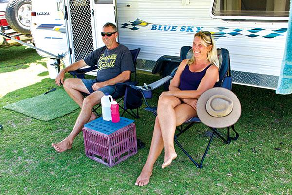Couple -using -multi -purpose -milk -crate -next -to -a -Blue -Sky -caravan