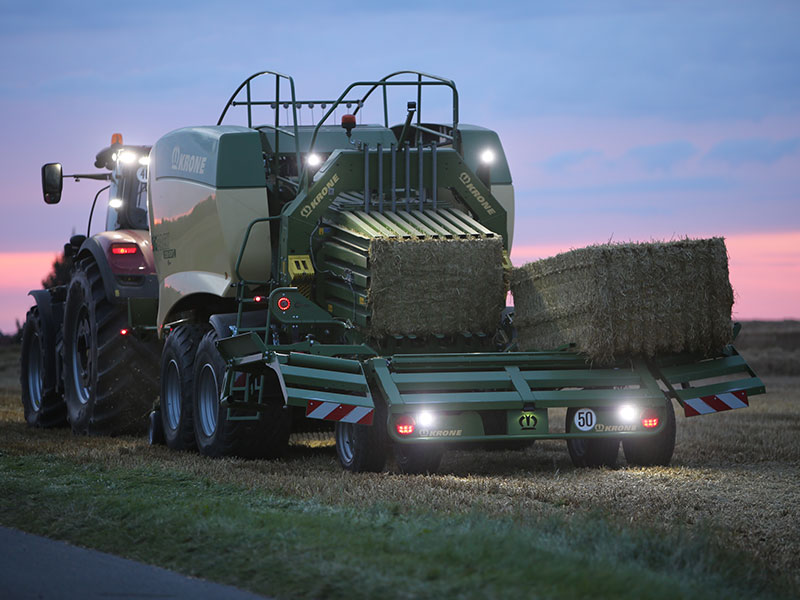 A Kubota tractor towing a Krone bale
