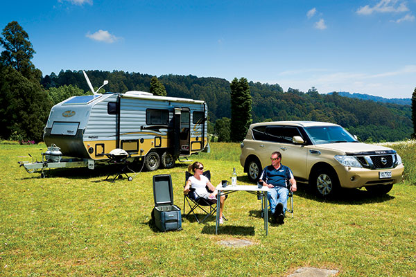 People -sitting -in -camping -chairs -next -to -a -caravan
