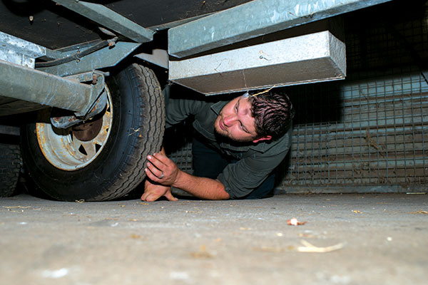 Inspecting -second -hand -camper -trailer -undercarriage