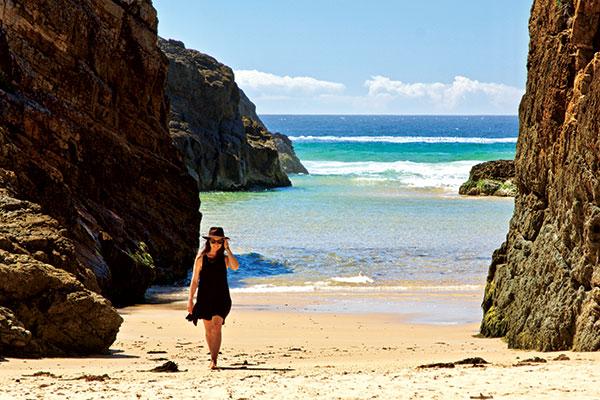 Woman -walking -on -the -beach -at -Bournda -Wallagoot -Gap -NSW