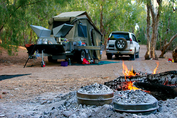 Campsite -with -camper -trailer -setup -next -to -a -car -and -campfire