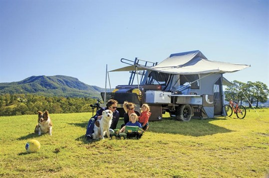 family and dog with a camper trailer
