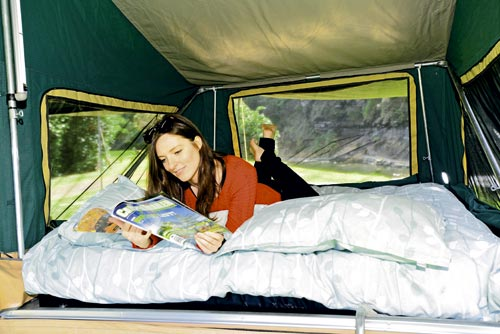 Woman In Bed Of A Camper Trailer