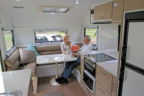 Man And Woman Sitting In Caravan Dinette
