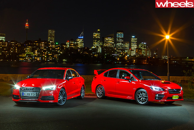 Audi -S3-vs -Subaru -WRX-STi --parked -in -front -of -city