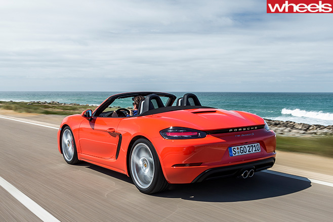 Orange -Porsche -918-Boxster -S-driving -rear -side