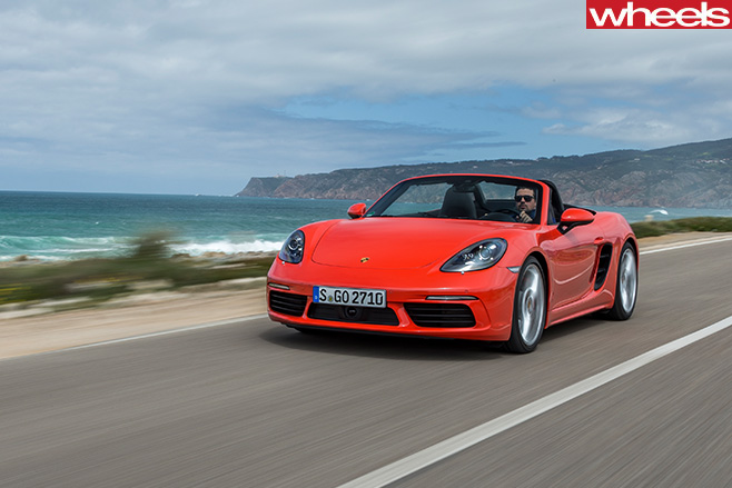 Orange -Porsche -918-Boxster -S-driving -side -front
