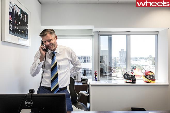 James -Warburton -standing -front -of -desk -on -phone