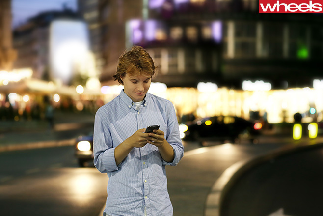 Young -man -texting -on -side -of -road