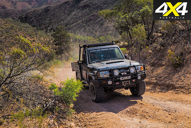 Red desert Land Cruiser driving uphill